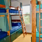 six bed dorm room with queen bed bunk beds and blue bedding